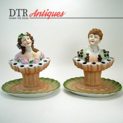 Pair of hand-painted bisque porcelain flower frogs depicting an aristocratic boy and girl from the turn of the century