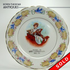 Porcelain advertising calendar plate with hand-painted blue birds and woman driving car from Gately Fitzgerald & Co., Erie, PA
