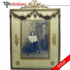 Gilt bronze Victorian picture frame with silk border and roses, and a portrait of a girl in a chair
