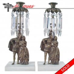 Pair of brass candelabras depicting a lady and lord on a marble plinth with cut glass prism spears