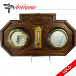Hall-hanging thermometer, barometer and hygrometer instruments on a wooden plaque