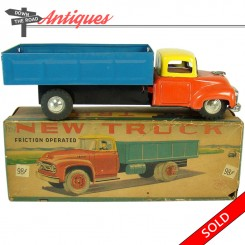 Red, blue and yellow tin friction truck toy, mint in the original box with rubber tires