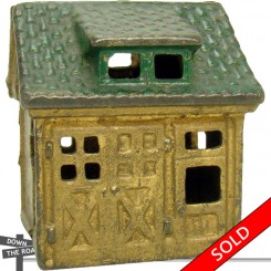 Antique cast iron still bank depicting a gold-colored garage with green roof