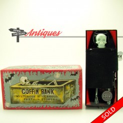 Tin skeleton and coffin wind-up toy bank in the original box by Yone Toys